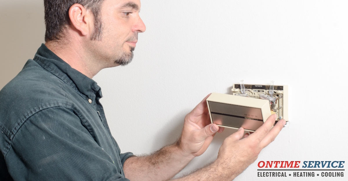 man changing thermostat battery